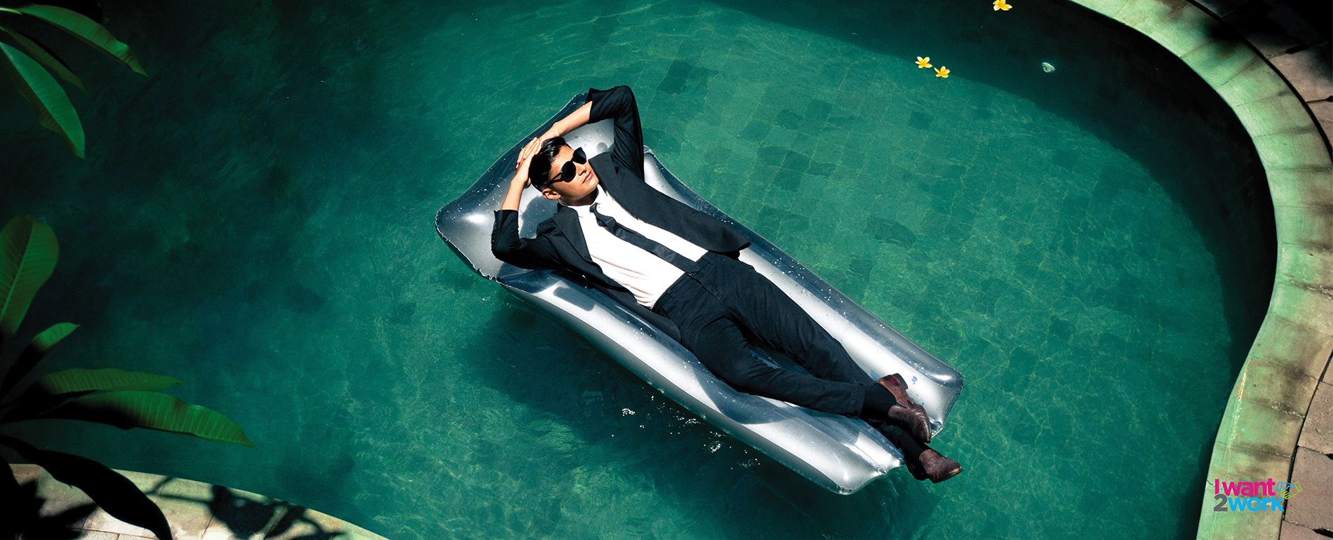 4 ways to end the business working year on a high guy man male on pool inflatable lilo in business suit working relaxed